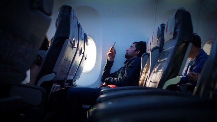 person watching movies while sitting in plane
